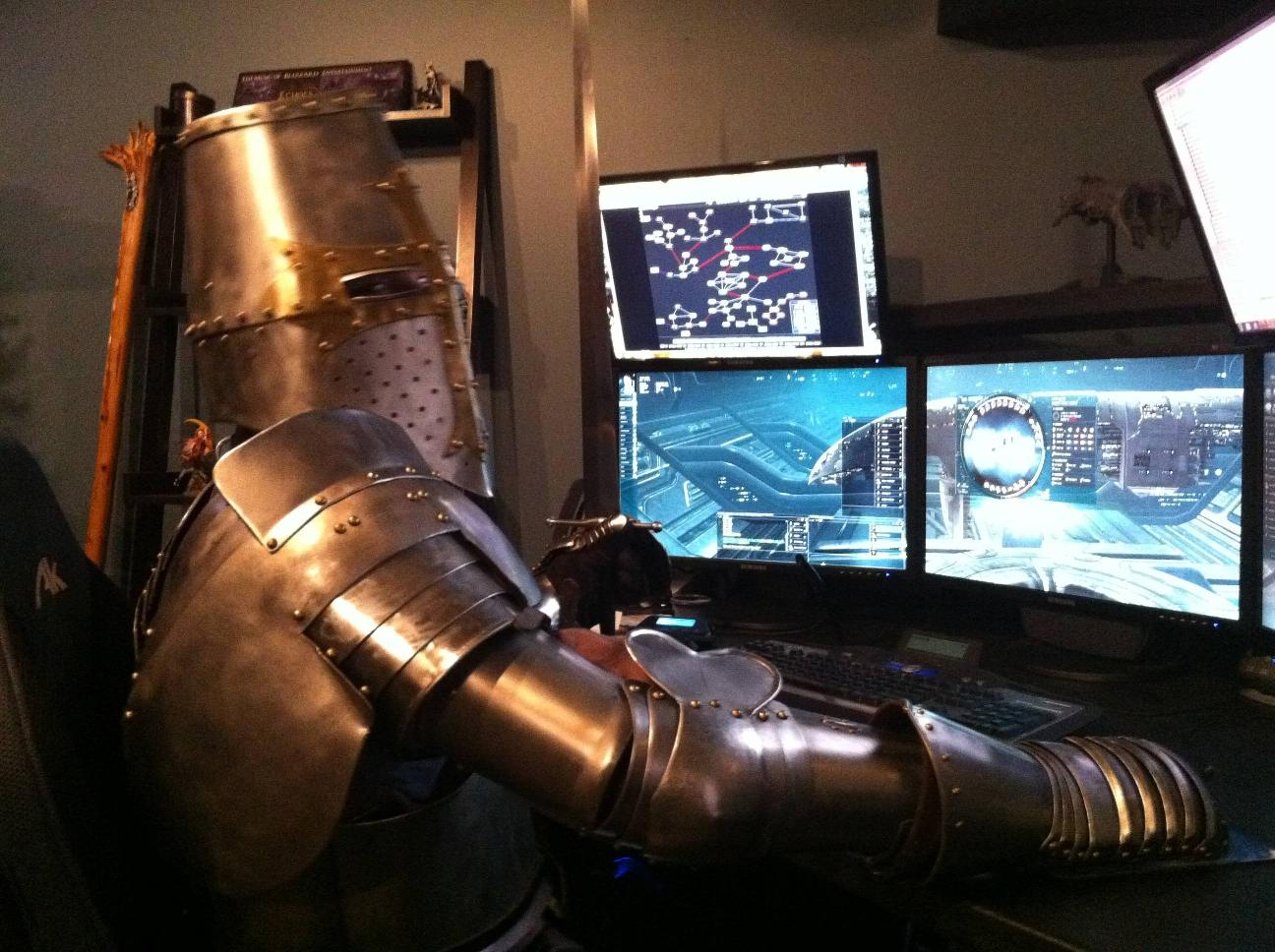 Armored Knight Sits at keyboard with four monitors, playing EVE Online.